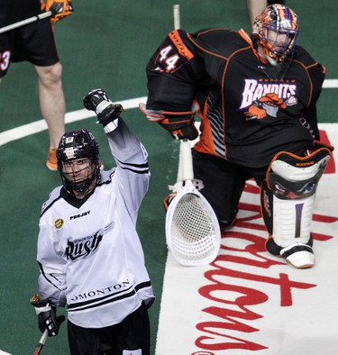 The Edmonton Rush's Zack Greer's (88) celebrates his hat-trick goal against the Buffalo Bandits during second half National Lacrosse League action at Rexall Place, in Edmonton Alta., on Friday March 21, 2014. The Buffalo Bandits' goaltender Anthony Cosmo (44) is pictured behind Greer. David Bloom/Edmonton Sun/QMI Agency