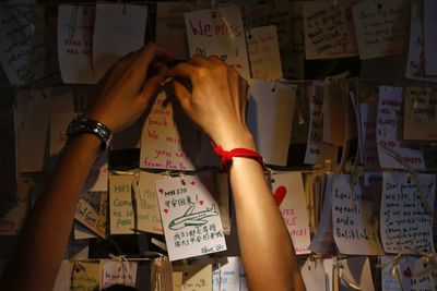 A woman hangs another message of hope and support for the passengers of the missing Malaysia Airlines MH370 at a mall outside Kuala Lumpur March 22, 2014. Two weeks after a Malaysian airliner carrying 239 people vanished, international teams stepped up their search deep in the southern Indian Ocean on Saturday, as a Malaysian minister expressed fear a possible sighting of debris may be another false lead.  REUTERS/Damir Sagolj