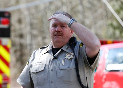 Snohomish County Sheriff Ty Trenary looks on as landslide blocks Highway 530 near Oso, Washington March 23, 2014. Eighteen people remain unaccounted for in a landslide that killed three and injured at least eight more in northwestern Washington state, officials said Sunday.  REUTERS/Lindsey Wasson/Pool