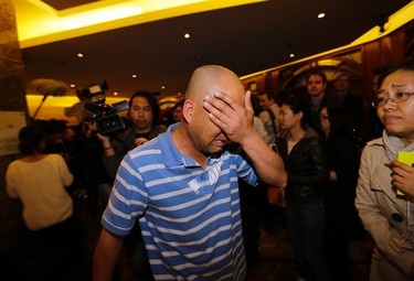 A family member of a passenger aboard Malaysia Airlines MH370 cries after watching a television broadcast of a news conference, at Lido hotel in Beijing, March 24, 2014. Relatives of Chinese passengers aboard the missing Malaysia Airlines flight reacted with hysteria on Monday after the Malaysian prime minister announced the jet ended its journey in the remote Southern Indian Ocean. REUTERS/Jason Lee