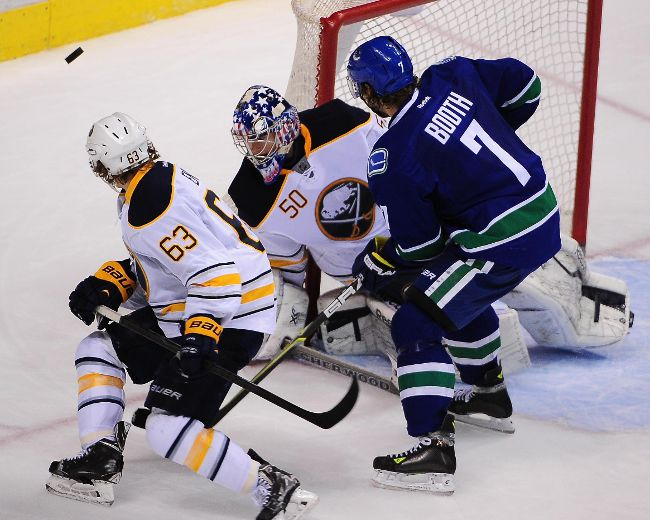 Vancouver Canucks forward David Booth (7) shoots the puck against Buffalo Sabres goaltender Nathan Lieuwen (50) and forward Tyler Ennis (63) during the third period at Rogers Arena, March 23, 2014 in Vancouver, B.C. The Vancouver Canucks won 4-2. (Photo: Anne-Marie Sorvin-USA TODAY Sports)
