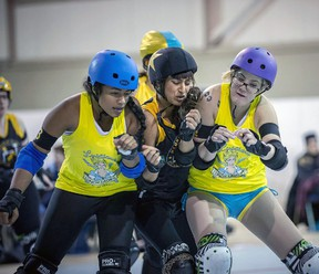 A group of roller derby competitors crush together during competition. Roller derby had its heyday in the 1970s but has been rising in popularity in the last 10 years.  (Mark Girdauskus at Photos by MG)