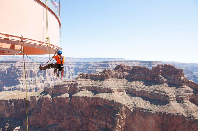 A technician from Abseilon USA works to clean more than 40 panes of glass underneath the horseshoe-shaped bridge at the Grand Canyon Skywalk in Arizona in this handout picture courtesy of George & Pat Walsh of GPWalshPhotography.com, taken March 24, 2014. REUTERS/George & Pat Walsh of GPWalshPhotography.com/Handout via Reuters