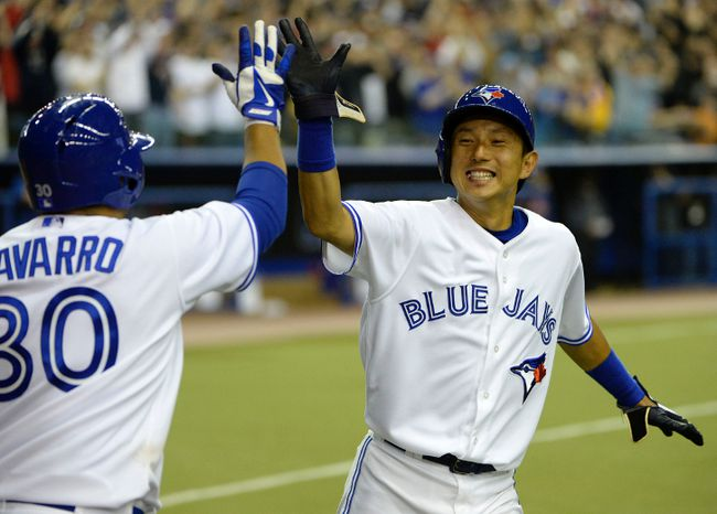 Blue Jays shortstop Munenori Kawasaki celebrates with catcher Dioner Navarro after scoring the winning run in the ninth inning against the New York Mets at the Olympic Stadium on Friday. (Eric Bolte-USA TODAY Sports)