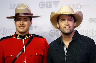 Dean Brody poses with an RCMP Constable as he arrives on the red carpet at the 2014 Juno Awards in Winnipeg March 30, 2014. REUTERS/Trevor Hagan
