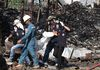Rescue workers walk amongst debris as they carry a body away from the scene of an explosion at a metal recycling shop in Bangkok on April 2, 2014. (REUTERS/Stringer)