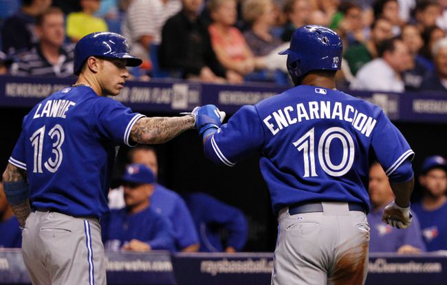 Toronto Blue Jays first baseman Edwin Encarnacion (10) is congratulated by third baseman Brett Lawrie (13) after he scored a run during the fourth inning against the Tampa Bay Rays on April 2. (Kim Klement-USA TODAY Sports)