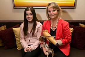 Alex Falardeau, 14 and her mom Kelly Falardeau pose with a prosthetic arm on Monday. Kelly is a burn victim who is raising fundds for an African man, also a burn victim. (Codie McLachlan/Edmonton Sun)