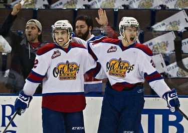 Edmonton's Ben Carroll, left, and Mads Eller, right, celebrate Eller's goal on Brandon's Jordan Papirny (not pictured) during the first period of the Edmonton Oil Kings' WHL playoff hockey game against the Brandon Wheat Kings at Rexall Place in Edmonton, Alta., on Thursday, April 3, 2014. Codie McLachlan/Edmonton Sun/QMI Agency