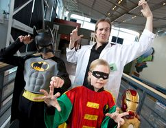 Dr. Yann Brouillette poses for a photo with Batman a.k.a Nathan Shaw, 10, Robin a.k.a. Alexis Shaw, 8, and Iron Man a.k.a. Andrew Shaw, 5, at the Telus World of Science on Thursday. Brouillette presented his talk, titled Comic Book Chemistry: Science vs Superheroes & Villains at the science centre.
