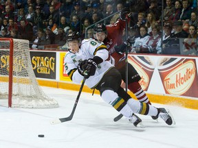 London Knights defenceman Nikita Zadorov is tripped by Storm forward Scott Kosmachuk during the first period of Game 1 of the OHL Western Conference semifinal at the Sleeman Centre in Guelph.  (CRAIG GLOVER, The London Free Press)