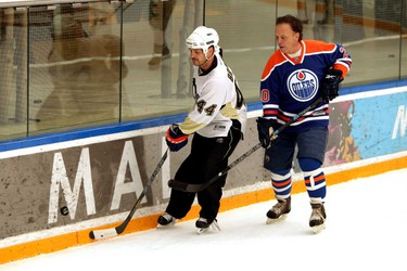 Oilers alumni Rob Brown (l) and Dave Lumley looks for a loose puck.  Edmonton Oilers alumni reunite for a friendly game against the media to launch Alzheimer�s Face Off at West Edmonton Mall in Edmonton, Alberta on Monday, Apr 8, 2014.  The Alzheimer Society of Alberta and Northwest Territories brings pro-am hockey event back to Edmonton, April 11 � 13, 2014.  This will mark the official kick-off for the annual pro-am tournament, which raises critical research dollars for the Alzheimer Society.    Perry Mah/ Edmonton Sun/ QMI Agency