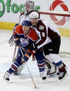 Oilers forward Ryan Smyth refuses to budge from the lip of the crease, despite the best efforts of Colorado's Jan Hejda and goalie Jean-Sebastien Giguere at Rexall Place Tuesday. (David Bloom, Edmonton Sun)