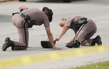 Highway Patrol officers investigate tire skid marks after several children were injured after being struck by a vehicle at a KinderCare Learning Center in Winter Park, Florida April 9, 2014. One child died and a dozen people were injured in a hit-and-run crash at an Orlando-area daycare centre on Wednesday afternoon, according to media reports citing hospital officials.  REUTERS/Stephen M. Dowell/Orlando Sentinel