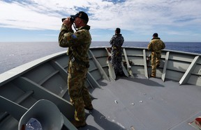 Gunner Richard Brown (L) of Transit Security Element looks through binoculars as he stands on lookout with other crew members aboard the Australian Navy ship HMAS Perth as they continue to search for missing Malaysian Airlines flight MH370.  Australian Defence Force/Handout via Reuters