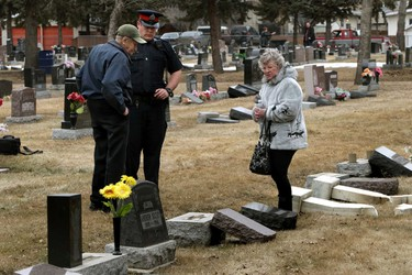 John Hutzcal (l) and Frances Fedorko speaks to Const. Liam Watson about the damage to headstones.  The Edmonton Police Service is investigating a overnight vandalism spree at St. Michael's Cemetery  in north end of Edmonton, Alberta on Thursday, Apr 10, 2014.  Perry Mah/ Edmonton Sun/ QMI Agency