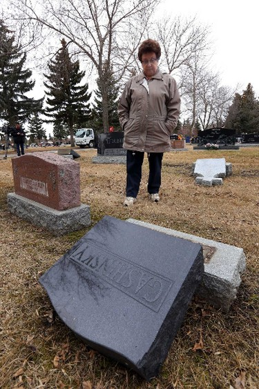 Elizabeth Sproule looks at the damage to her brother in law's headstone.  The Edmonton Police Service is investigating a overnight vandalism spree at St. Michael's Cemetery  in north end of Edmonton, Alberta on Thursday, Apr 10, 2014.  Perry Mah/ Edmonton Sun/ QMI Agency