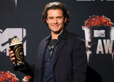 """Actor Orlando Bloom poses backstage with his award for Best Fight for """"The Hobbit: The Desolation of Smaug"""" during the 2014 MTV Movie Awards in Los Angeles, California  April 13, 2014. (REUTERS/Danny Moloshok)"""