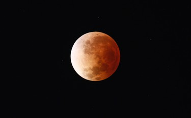 The moon is seen as it begins a total lunar eclipse that will turn the moon red over Buenos Aires on April 15, 2014. (REUTERS/Marcos Brindicci)