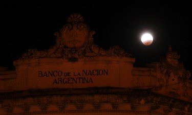The moon is seen behind a National Bank of Argentina branch at the end of a total lunar eclipse in Buenos Aires on April 15, 2014. (REUTERS/Marcos Brindicci)