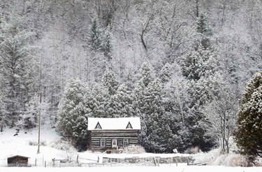 Snow covers a log cabin off Highway 36 in the City of Kawartha Lakes in central Ontario on April 15, 2014. Most of the province saw snow this morning one of the latest spring snowfalls in recent history. (REUTERS/Fred Thornhill)