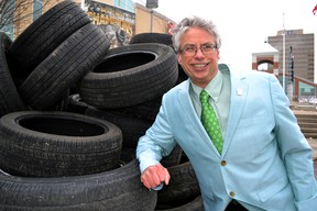 Jay Stanford, director, environment, fleet and solid waste for the City of London, leans against a pile of 110 tires in front of Budweiser Gardens April 15, 2014 in London, Ont. Stanford launched the 19th London Clean and Green, 12 days of environment cleaning initiatives that includes free tire recycling. CHRIS MONTANINI\LONDONER\QMI AGENCY