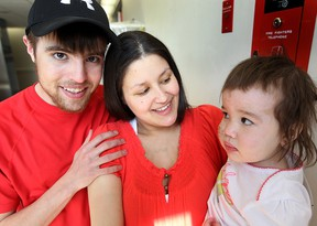 Paul Nault (left) and Michelle Abdilla hold their 18 month old daughter Arianna in Winnipeg, Man. Tuesday April 15, 2014. The trio escaped a house fire in St. Georges last month. (Brian Donogh/Winnipeg Sun)