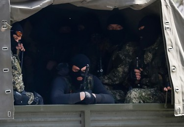 Armed men, wearing black and orange ribbons of St. George - a symbol widely associated with pro-Russian protests in Ukraine, drive a car in Slaviansk April 18, 2014. The self-declared leader of pro-Russian separatists in eastern Ukraine, Denis Pushilin, on Friday said that he did not consider his men to be bound by an agreement between Russia and Ukraine to disarm and vacate occupied buildings.  REUTERS/Gleb Garanich
