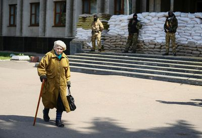 An elderly woman passes by as armed men, who are wearing black and orange ribbons of St. George - a symbol widely associated with pro-Russian protests in Ukraine, stand guard in front of barricades outside the mayor's office in Slaviansk April 18, 2014. The self-declared leader of pro-Russian separatists in eastern Ukraine, Denis Pushilin, on Friday said that he did not consider his men to be bound by an agreement between Russia and Ukraine to disarm and vacate occupied buildings.  REUTERS/Gleb Garanich