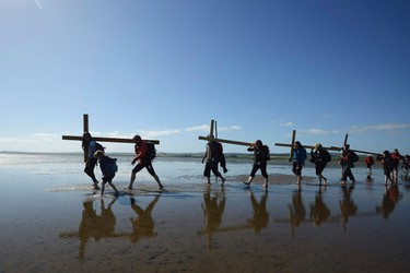 Pilgrims walk across a tidal causeway while carrying crosses during the final leg of the Northern Cross pilgrimage to Holy Island in Northumbria, northern England April 18, 2014. For more than thirty years Christians have taken part in the pilgrimage to Holy Island, walking through Northumberland and the Scottish Borders, during Holy Week. REUTERS/Nigel Roddis