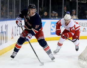 Ryan McDonagh #27 of the New York Rangers takes the puck as Gustav Nyquist #14 of the Detroit Red Wings defends at Madison Square Garden on March 9, 2014 in New York City. (Elsa/Getty Images/AFP)