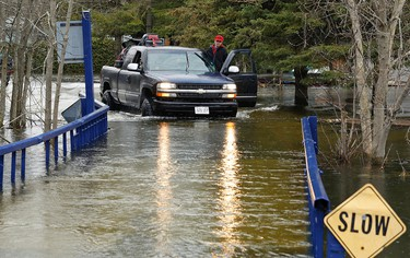 A motorist attempts to cross a flooded access bridge as water from the Otonabee River continues to rise on Friday, April 18, 2014 at Driscoll Cottages south of  Peterborough. Clifford Skarstedt/Peterborough Examiner/QMI Agency