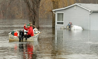 Jade Fife, James McGreevy and Frank the dog use their boat to access their flooded property as water from the Otonabee River continues to rise on Friday, April 18, 2014 at Driscoll Cottages south of  Peterborough. Clifford Skarstedt/Peterborough Examiner/QMI Agency