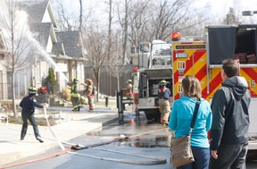A West Hill townhouse, off Morrish Rd., was gutted by a fire that began in the garage Saturday. Shocked residents look on as Toronto firefighters, battle the blaze. The back of pumper 215 can be seen on the extreme right of the photo. (Chris Doucette/Toronto Sun)