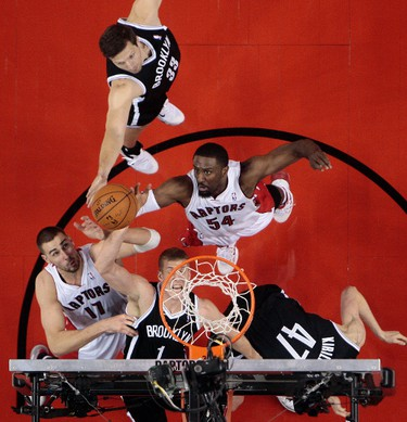 Jonas Valanciunas and Patrick Patterson of the Toronto Raptors put one in past Mason Plumlee of the Brooklyn Nets during Game 2 of the Eastern Conference playoffs at the Air Canada Centre in Toronto Tuesday, April 22, 2014. Dave Abel/Toronto Sun/QMI Agency