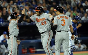 Baltimore Orioles designated hitter Nelson Cruz (23) is greeted at home plate by Orioles left fielder Ryan Lough (9) and third baseman Ryan Flaherty (3) after hitting a grand slam home run against Toronto Blue Jays at Rogers Centre Wednesday night. (Dan Hamilton-USA TODAY Sports)