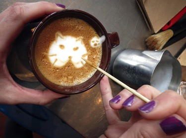 """A worker makes the image of a cat on a """"Cat'achino"""" at the cat cafe in New York April 23, 2014. The cat cafe is a pop-up promotional cafe that features cats and beverages in the Bowery section of Manhattan.     REUTERS/Carlo Allegri"""