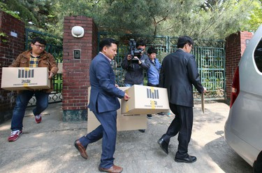Officials from the Incheon District Prosecutors' office carry boxes during a raid of the home of Yoo Byung-un, in Seoul April 23, 2014. South Korean prosecutors investigating the fatal sinking of the Sewol ferry on Wednesday raided the home of Yoo, the head of a family that owns the Chonghaejin Marine Co. Ltd, the company that operated the vessel.  Yonhap news agency reported that Yoo's home and a church in which he is believed to have an interest were raided. The prosecutors' office declined to comment and Reuters correspondents at the church in Seoul said it had been locked. REUTERS/Yonhap