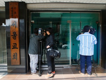 South Korean journalists stand outside the Seoul branch of the Evangelical Baptist Church April 23, 2014. South Korean prosecutors investigating the fatal sinking of the Sewol ferry on Wednesday raided the home of Yoo Byung-un, the head of a family that owns the Chonghaejin Marine Co. Ltd, the company that operated the vessel. Yonhap news agency reported that Yoo's home and the Seoul branch of the Evangelical Baptist, in which he is believed to have an interest, were raided. The prosecutors' office declined to comment and Reuters correspondents at the church in Seoul said it had been locked.    REUTERS/James