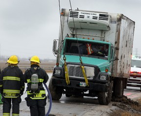 Winnipeg firefighters watch as a 5 ton is righted following a rollover at Highway 7 and the Perimeter in Winnipeg, Man. Thursday April 24, 2014. The extent of injuries to the driver is unknown. (Brian Donogh/Winnipeg Sun)