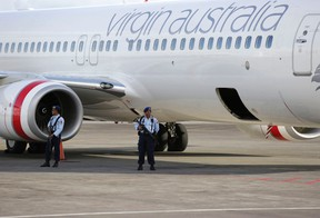 Indonesian air force soldiers hold rifles they guard near a Virgin Australia airplane at Denpasar airport in the resort island of Bali April 25, 2014. The pilot of a Virgin Australia plane flying from Brisbane to Bali on Friday reported a hijacking attempt. REUTERS/Stringer