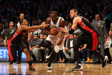 Brooklyn Nets centre Andray Blatche drives between Toronto Raptors guard Kyle Lowry (7) and forward Amir Johnson (15) during the fourth quarter in Game 3 on April 25. (Anthony Gruppuso-USA TODAY Sports)