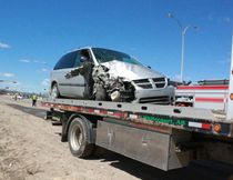 The silver minivan that struck the Whitecourt Fire vehicle head-on sits on a tow truck. Police are investigating the accident. 
