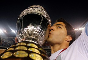Uruguay's Luis Suarez kisses the trophy after winning the Copa America final soccer match against Paraguay in Buenos Aires, July 24, 2011.  (REUTERS/Enrique Marcarian)