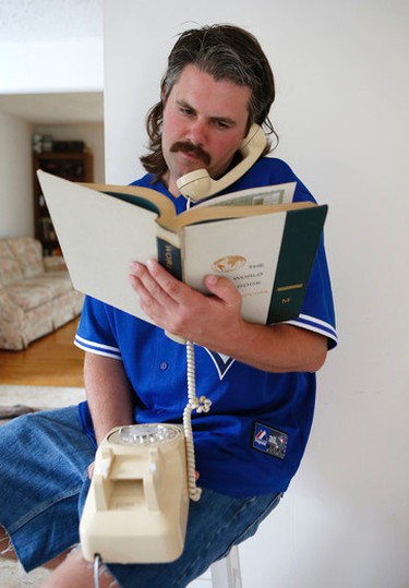 Blair McMillan has his hands full with an old school rotary phone and an encyclopedia  on Tuesday August 27, 2013.  McMillan has rid his family of all technolgy living his life as he did in 1986. Craig Robertson/Toronto Sun/QMI Agency