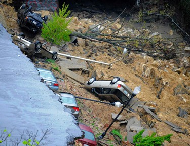 Multiple vehicles lie at the bottom of a landslide after heavy rains caused a street to give way in Baltimore, Maryland April 30,  2014.   REUTERS/Karl Merton Ferron/Baltimore Sun