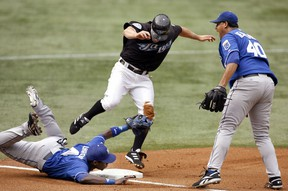 Kansas City Royals starting pitcher Runelvys Hernandez reacts as Toronto Blue Jays base runner Reed Johnson (C) is tagged out at third base by Angel Berroa (L) during the first inning of their game in 2006. (Reuters)