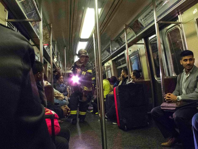 "A firefighter uses a flashlight as he makes his way past passengers through the derailed ""F"" train in the Woodside neighborhood located in the Queens borough of New York May 2, 2014. REUTERS/Connie Wang"