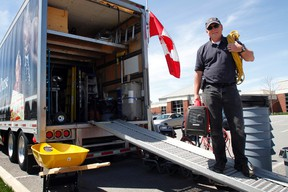 Samaritan's Purse regional representative Stephen Elliott carries generators and electric cords outside the non-profit, Christian charity's mobile headquarters at Maranatha Christian Reformed Church in Belleville, Ont. Monday, May 5, 2014. - JEROME LESSARD/THE INTELLIGENCER/QMI AGENCY