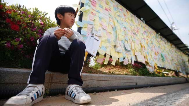 A boy sits next to a board with messages written for victims of sunken passenger ship Sewol, outside the official memorial altar in Ansan May 2, 2014.   REUTERS/Kim Hong-Ji